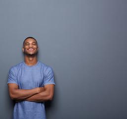Handsome african american man laughing with arms crossed
