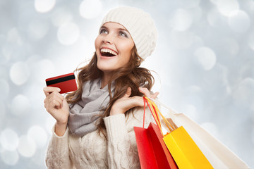Shopping happy woman holding bags and credit card. Winter sales.