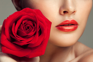 Young beauty model with red rose near lips