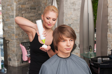 blond hairstylist female with hair mousse spray.