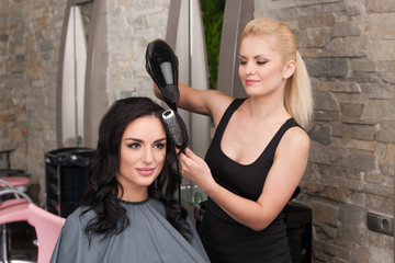 Beautician blow drying woman's hair after giving new haircut