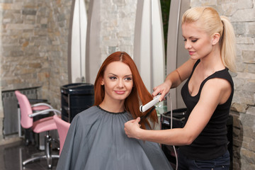 Hairdresser straightening red hair with hair irons.