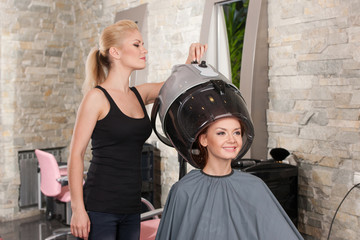 blond hairdresser adjusting hairdryer for client.