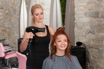 stylist drying redhead woman hair in salon.