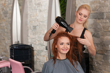 blond stylist drying redhead woman hair in salon.