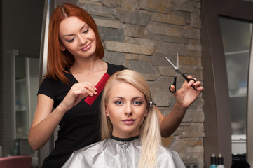 Happy young woman getting new haircut by hairdresser