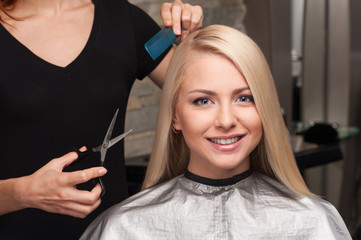 Happy young woman getting new haircut by hairdresser at parlor.