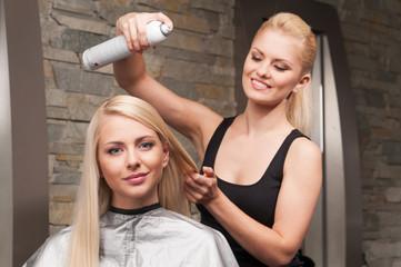 blond hairdresser applying spray on client's hair.