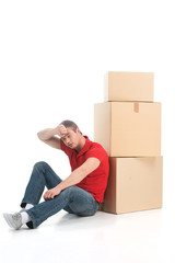 male sitting on floor tired of moving boxes.