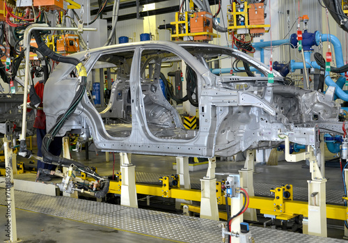 canvas print picture Spot contact welding of bodies of cars at automobile plant