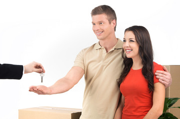 couple celebrating new home taking keys and moving boxes.