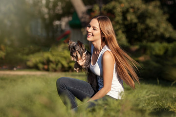 girl with long hair holding a dog