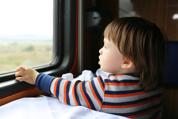 lovely boy looks out of window in the train
