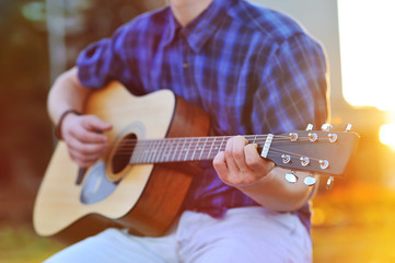 Close up portrait of male hands playing acoustic guitar