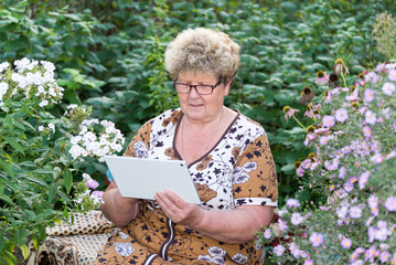 Senior woman using digital tablet in home garden