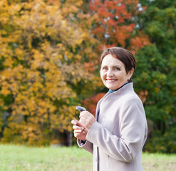 attractive woman 50 years in the autumn park