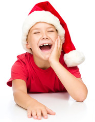 Little girl in santa hat is laughing