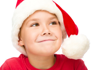 Little girl in santa hat is daydreaming
