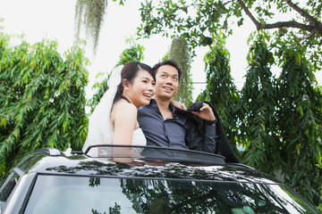 Bride and Groom Smiling Together While Standing in car