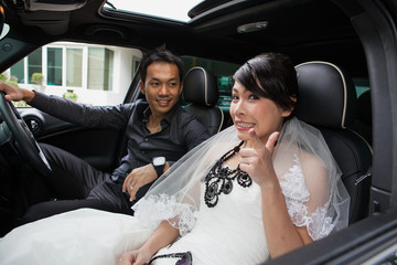gorgeous wedding couple in car