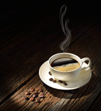 Fototapeta Kawa jest smaczna - Cup of coffee with smoke and coffee beans on old wooden table © amenic181