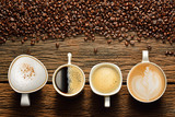 Variety of cups of coffee and coffee beans on old wooden table poster