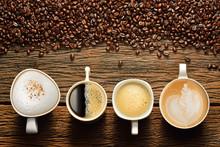 Vielzahl von Tassen Kaffee und Kaffeebohnen auf alten Holztisch