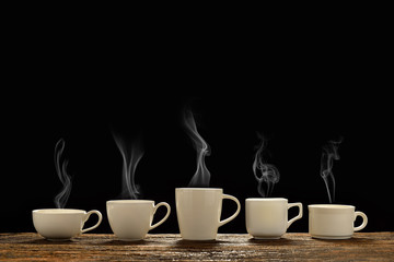 Variety of cups of coffee with smoke on black background © amenic181