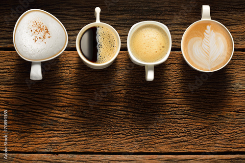Variety of cups of coffee on old wooden table - 70894365