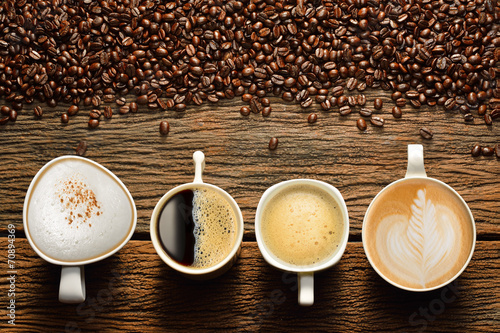 Fotobehang Koffiebonen Variety of cups of coffee and coffee beans on old wooden table