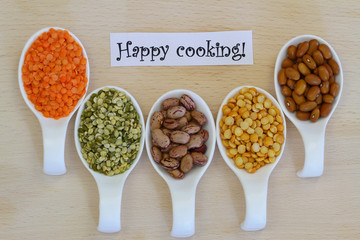 Happy cooking card with selection of pulses on porcelain spoons