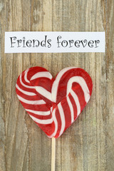 Friends forever card with heart shaped lollipop on wood