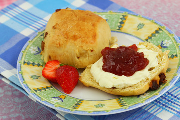 Scone with strawberry jam and clotted cream, close up