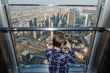 Little child taking photo of Dubai city from Burj Halifa.