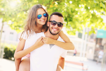 Happy couple doing piggyback in the park