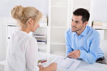 Beratungsgespräch: Kunde und Berater am Tisch
