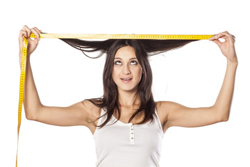 Funny attractive girl measured her hair with a tape measure