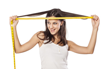 Happy attractive girl measured her hair with a tape measure