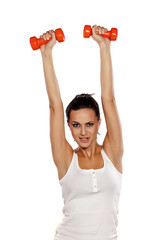 Happy attractive girl holding weights in her hands