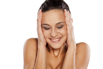 ashamed and smiling  woman holding her face with her hands