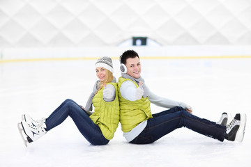 Cheerful couple sitting on the skating rink