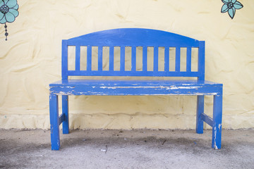 Blue wooden bench in front of pale yellow wall