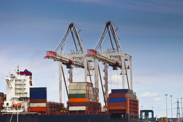 Container ship in a harbor with cranes moving cargo