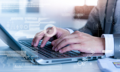 Close up of business man typing on laptop conputer with technolo