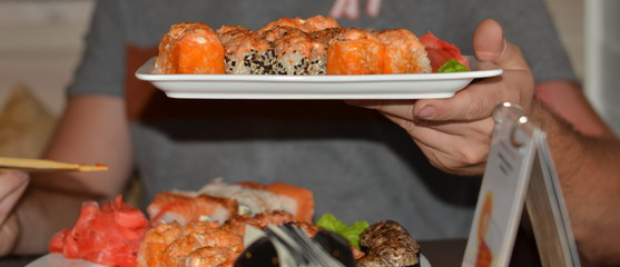 Man holds out a white plate with a Japanese rolls