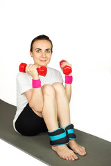 Young woman with dumbbells and ankle weights, isolated