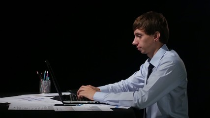 Businessman working with his laptop on black background