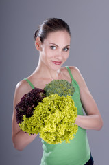 Woman with lettuce, cabbage and broccoli over gray background.