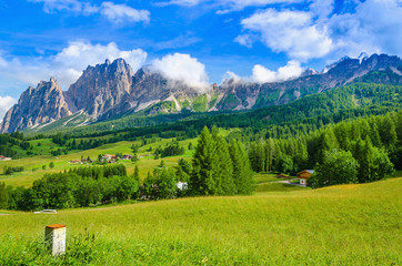 Green meadow and traditional houses in Dolomites, Italy