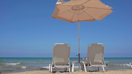 Sun umbrellas and chaise longues on beach.